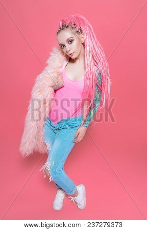 Stylish girl with pink dreadlocks posing in bright clothes on a pink background. Full length portrait. Beauty, fashion.