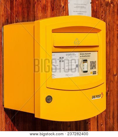 Filisur, Switzerland - 3 March, 2017: A Yellow Mail Box Of Swiss Post On A Wooden Wall, Main Focus O