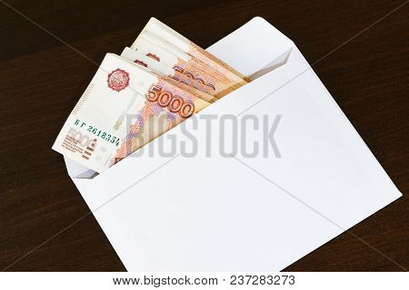 A White Envelope With A Pack Of Russian Five Thousand Ruble Banknotes Lies On A Dark Table