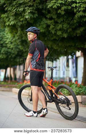 Back View Of Sporty Bicyclist Posing Near Bicycle Shooting For Sport Ad Cycling Garment Campaign. Yo