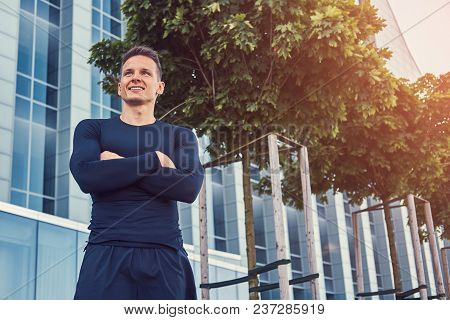 Smiling Handsome Man In A Black Sportswear, Standing With Crossed Arms In The Modern City Against A