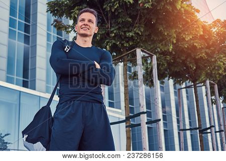 A Happy Handsome Man In A Black Sportswear, Standing With Crossed Arms In The Modern City Against A