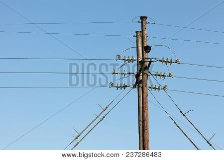 Power Line Supports Against A Blue Sky Background.