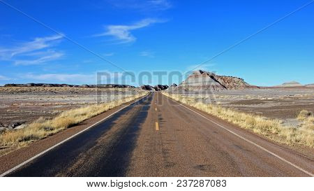 Road Running Through Badlands Landscape In Petrified Forest National Park, Arizona, Usa