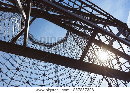 Bottom View Of Old Cooling Tower In Front Of Blue Sky With Sun