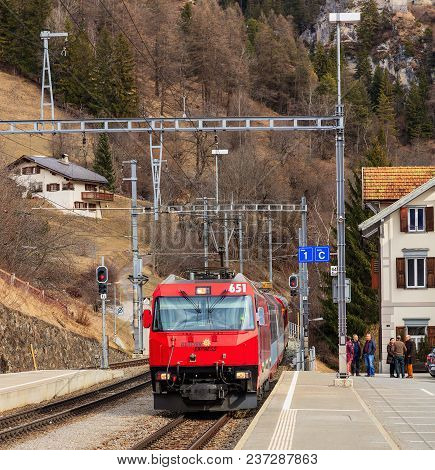 Filisur, Switzerland - 3 March, 2017: The Locomotive Of A Glacier Express Train Arriving To The Fili