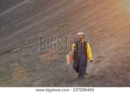 Man Walk On Volcano Ash In Sandboarding Tour In Nicaragua