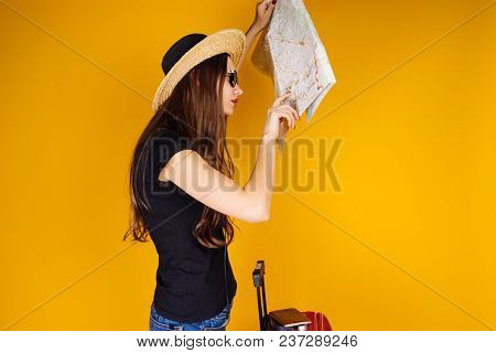 A Young Girl In A Straw Hat Travels With A Large Suitcase, Studies A Map Of The City