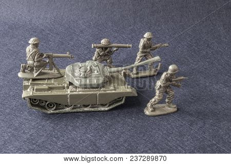 Plastic Small Toy Of Military Men With Weapons And Tank In Fighting At War. Soldier Battle Scene Wit