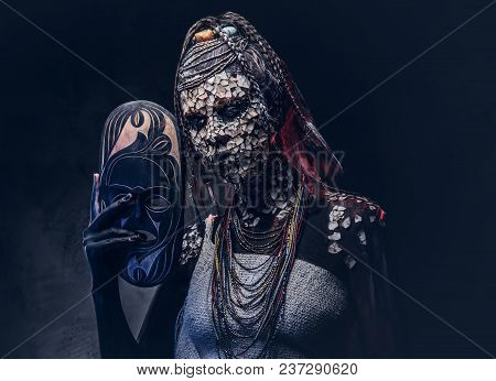 Portrait Of A Scary African Shaman Female With A Petrified Cracked Skin And Dreadlocks, Holds A Trad