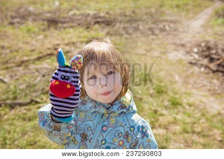 Beautiful Little Girl Playing Outdoors With A Toy In Hand