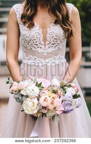 Brunette Bride In A Beautiful Pink Wedding Dress With Embroidery On A Corset Holding A Bouquet Of Pe