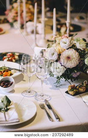 Banquet Table For Dinner Decorated With Flower Bouquets Of Dahlia And White Candles. On The Table, G