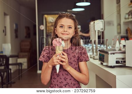 A Smiling Beauty Little Girl In A Fashionable Dress Holds Strawberry Ice Cream, Standing In An Ice C