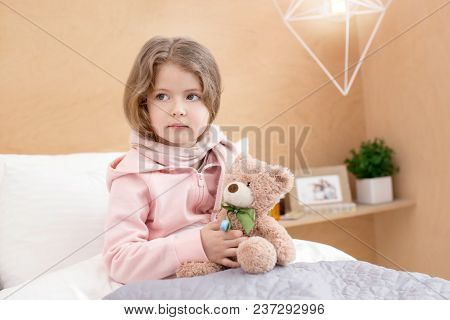 Having A Rest. Charming Little Girl Sitting On Her Bed And Holding Her Toy