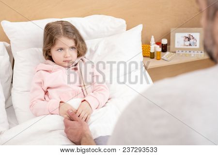 My Honey. Caring Worried Daddy Holding Her Daughters Hand And Girl Lying Sick In Bed