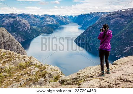 Nature photographer tourist with camera shoots while standing on top of the mountain. Beautiful Nature Norway Preikestolen or Prekestolen.