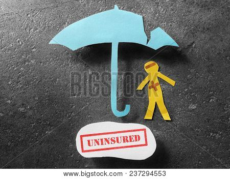 Bandaged Paper Man Under Cracked Umbrella With Uninsured Text Stamped Below