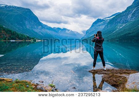 Nature photographer tourist with camera shoots Beautiful Nature Norway natural landscape. lovatnet lake.