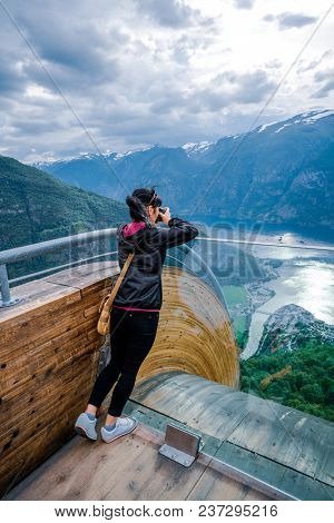 Nature photographer tourist with camera shoots. Stegastein Lookout. Beautiful Nature Norway.