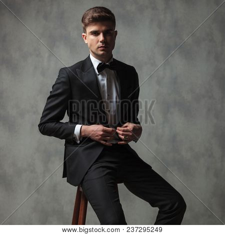 sexy businessman dressed formally buttoning his suit while sitting on a wooden chair on grey wall background