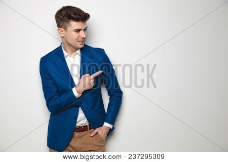 standing smart casual man looking and pointing to side while leaning against a white wall.