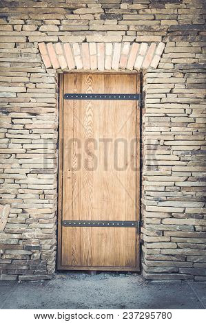 Old Wooden Door In A Stone Wall Back Background Texture.