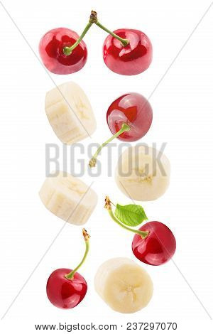 Isolated Falling Fruits. Falling Sliced Banana And  Cherries Isolated On White Background With Clipp