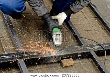 Worker In Gloves Cleans The Angle Grinder Metal Construction.