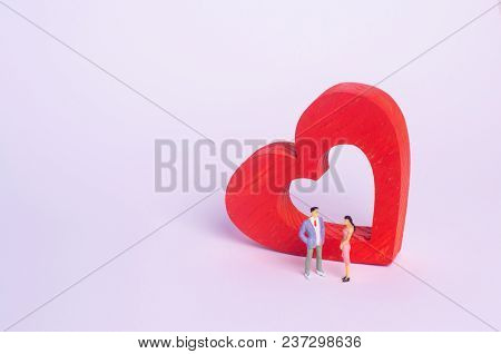People Stand And Speak Against The Background Of A Red Heart. The Man Is Talking To A Woman. Live Co