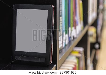 The Electronic Book On A Bookshelf Among The Many Books In The Library.