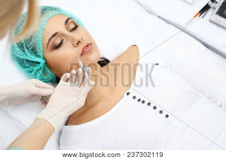 Professional Cosmetologist Making Injection In Face, Lips. Young Woman Gets Syringe With Filler For