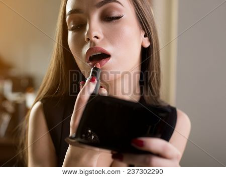 Tempting Look. Young Attractive Woman Is Looking At Mirror While Applying Lipstick On Her Lips. Make