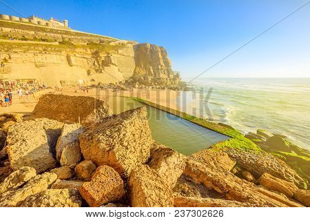 Scenic Promontory And Beach At Sunlight Of Azenhas Do Mar With Famous Natural Pool Visible At Low Ti