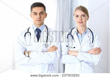 Doctors Standing Straight With Arms Crossed In Hospital. Physicians Ready To Help. Concept Of Health