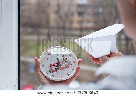 Moscow, Russia - April 22, 2018: The Girl Is Holding A Watch And A Paper Airplane. Action To Launch