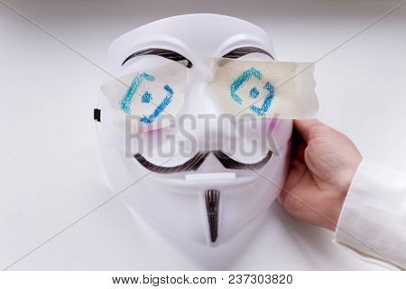 Moscow, Russia - April 22, 2018: Guy Fawkes Mask In His Hand. The Eyes Are Sealed With An Adhesive T