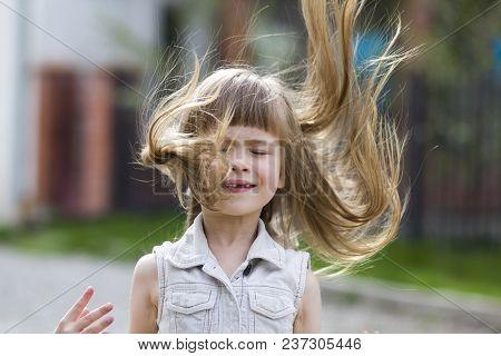 Pretty Little Preschool Girl In Sleeveless White Dress With Beautiful Long Blond Hair Blown By Wind,