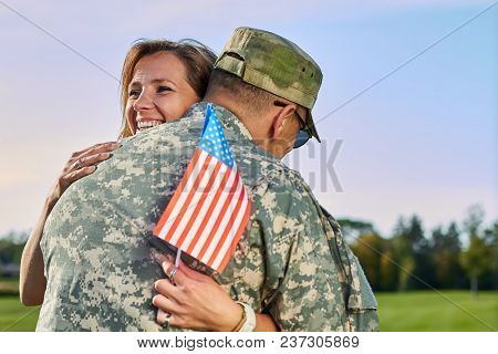Dating Of Happy Woman And Her Husband Us Army Soldier. Wife With Us Flag Is Hugging Her Military Hus