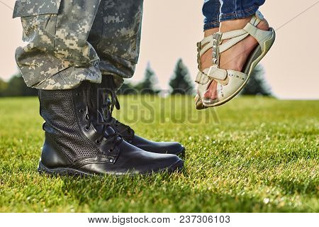 Soldier In Leather Boots And Girl In Sandals. Standing On The Grass, Lifting Up Daugther.