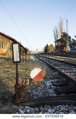Old Rusty Railway Switch With Red And White Colors Next To Rails At Sunset