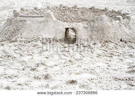 Sandcastle Constructed On A Sandy Beach With Opening