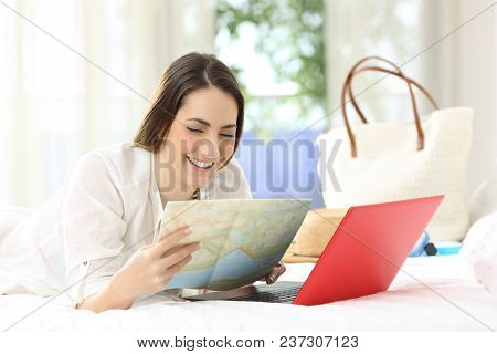 Happy Hotel Guest Planning Vacations With A Guide And A Laptop Lying On A Bed