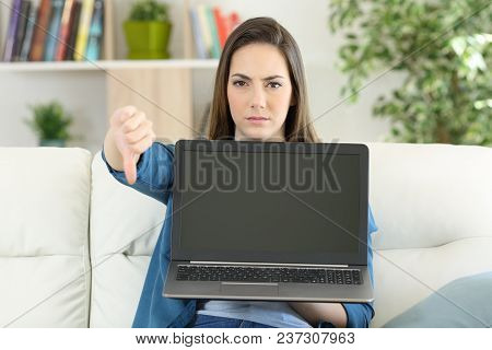 Anwry Woman Showing A Blank Laptop Screen Sitting On A Couch In The Living Room At Home