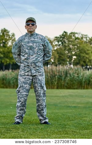 Sergeant In Camouflage Uniform Is Stanidng On The Grass. Portrait Of Full-length Soldier In The Park
