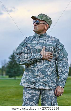 Patriotic Soldier In Uniform Outdoors. Portrait Of Brave Patriotic Sergeant With Sunglasses.