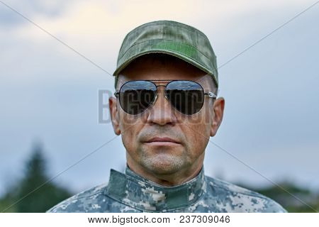 Close Up Portrait Of Strong Serious Soldier. Sergeant With Sunglasses And Cap. Cool And Strong Man W