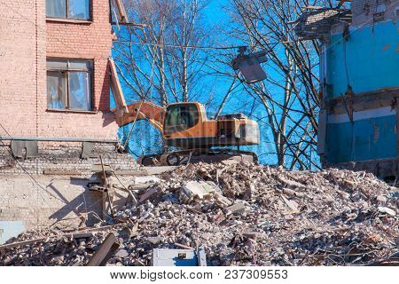 Excavator Destroys And Ruins The Building On A Bright Sunny Day.