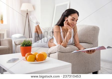 Favorite Pastime. Adorable Young Woman Lying On The Couch Comfortably And Reading A Magazine While S