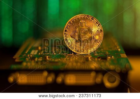 Bitcoin Closeup On A Mining Graphic Card With Matrix Background
